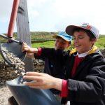 School boys filtering rocks into a pipe