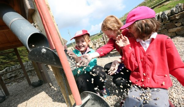 School children playing with gravel pipe