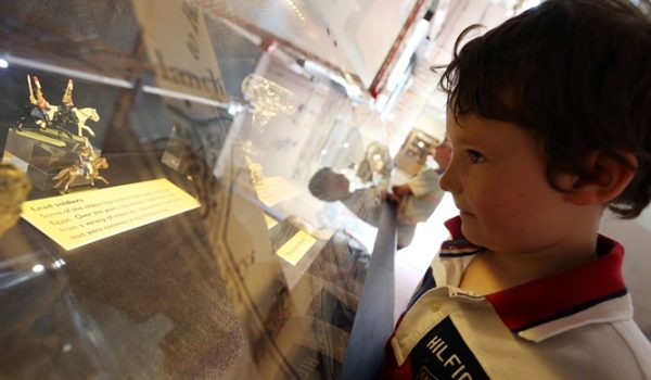 Child looking at small figurines in museum display