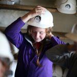 Young school girl putting her Killhope mining helmet on